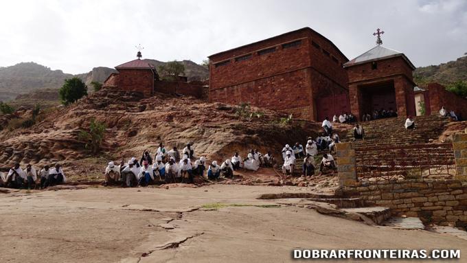 Homens em oração junto à igreja de Abraha We Atsbeha