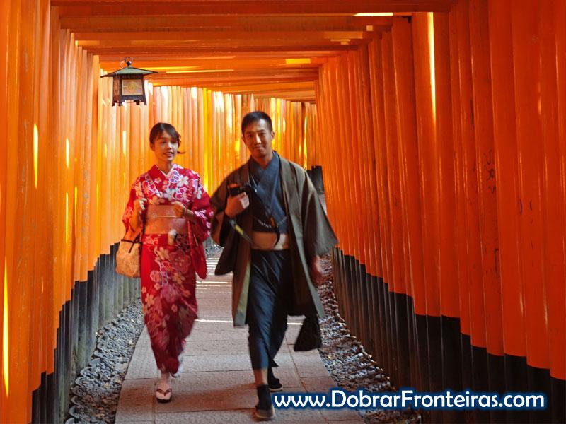 Casal de japoneses usando roupas típicas no meio dos Torii
