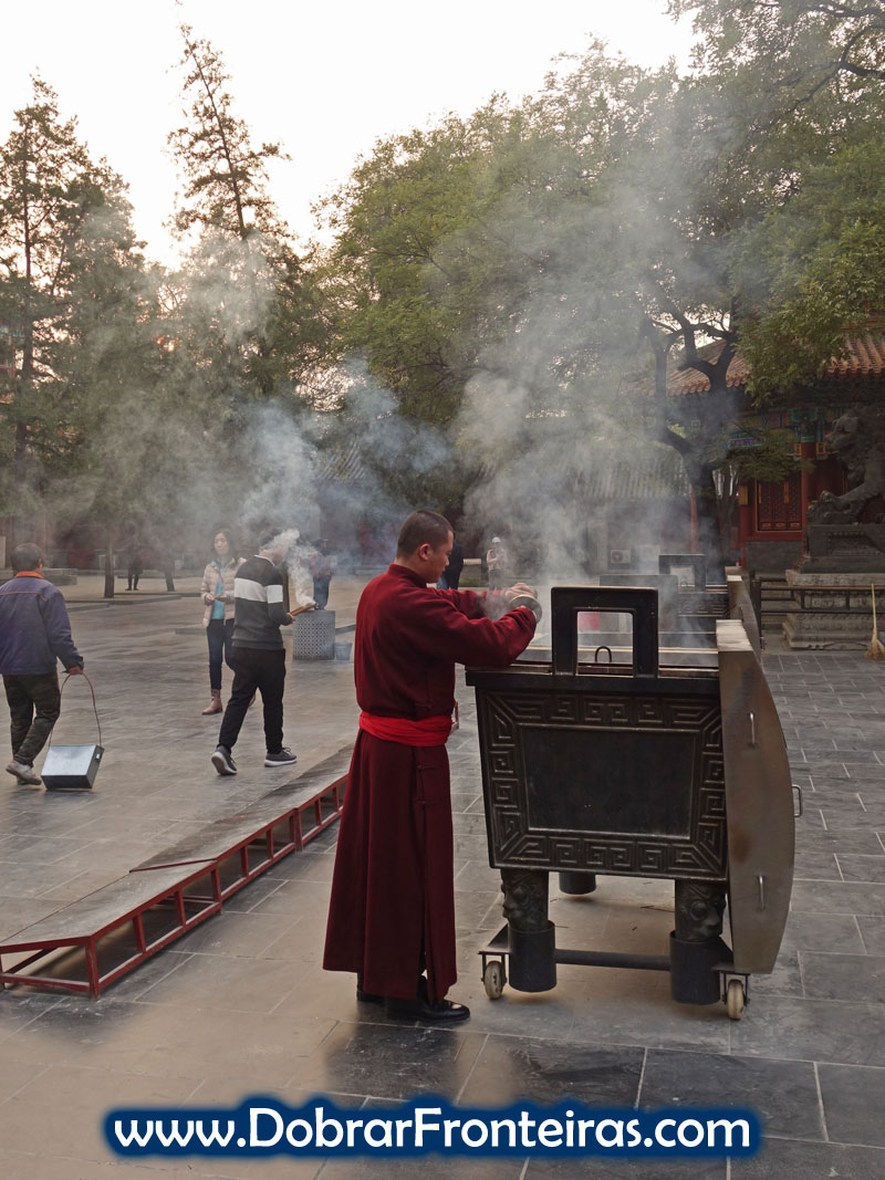 Monge queimando incenso no templo Lama