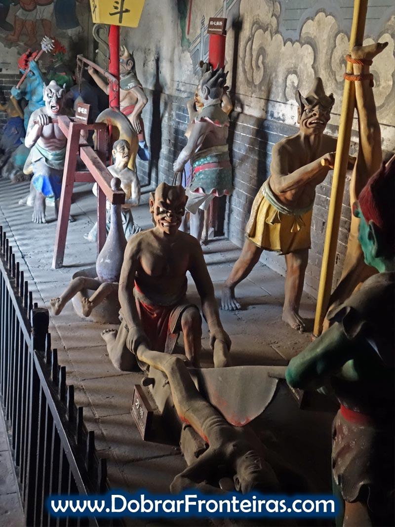 Figuras de demónios a torturar e cortar humanos no templo do Deus da Cidade em Pingayo, China