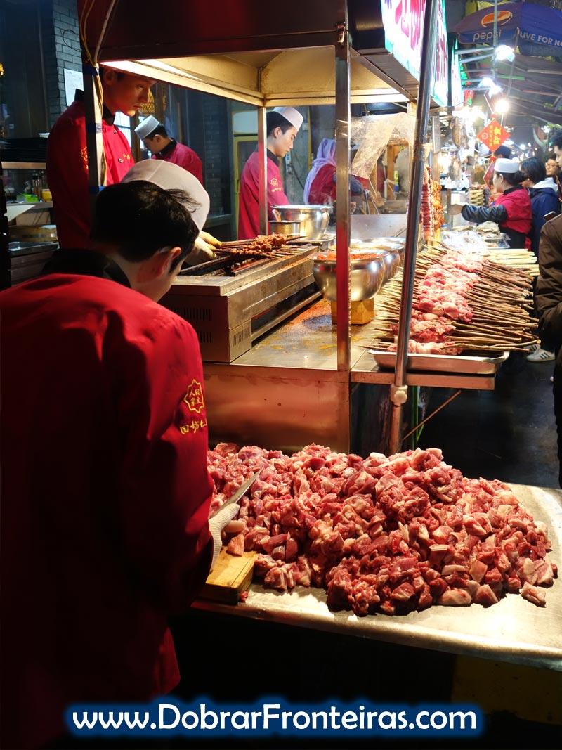 Rapaz prepara carne para as espetadas nas ruas de Xi'an, China