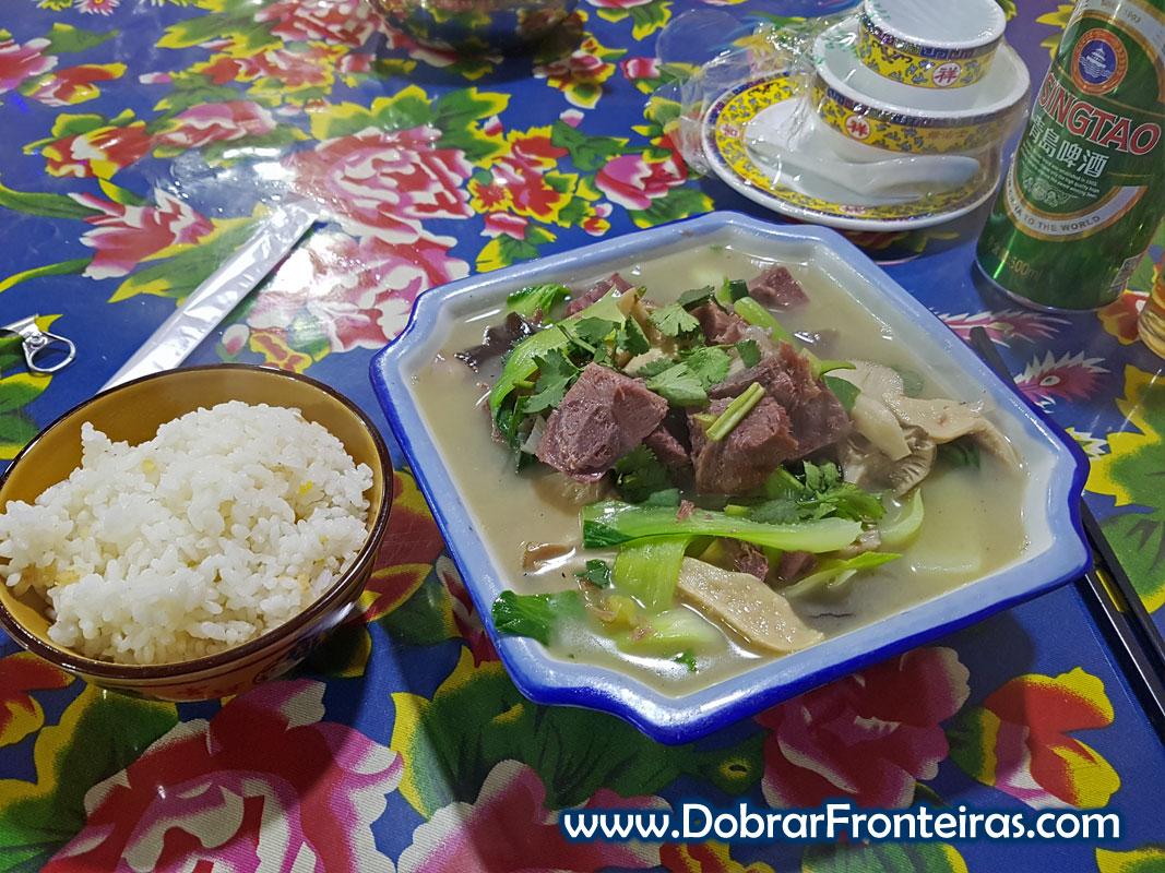 Prato de sopa de vaca e taça de arroz e cerveja chinesa em restaurante na China
