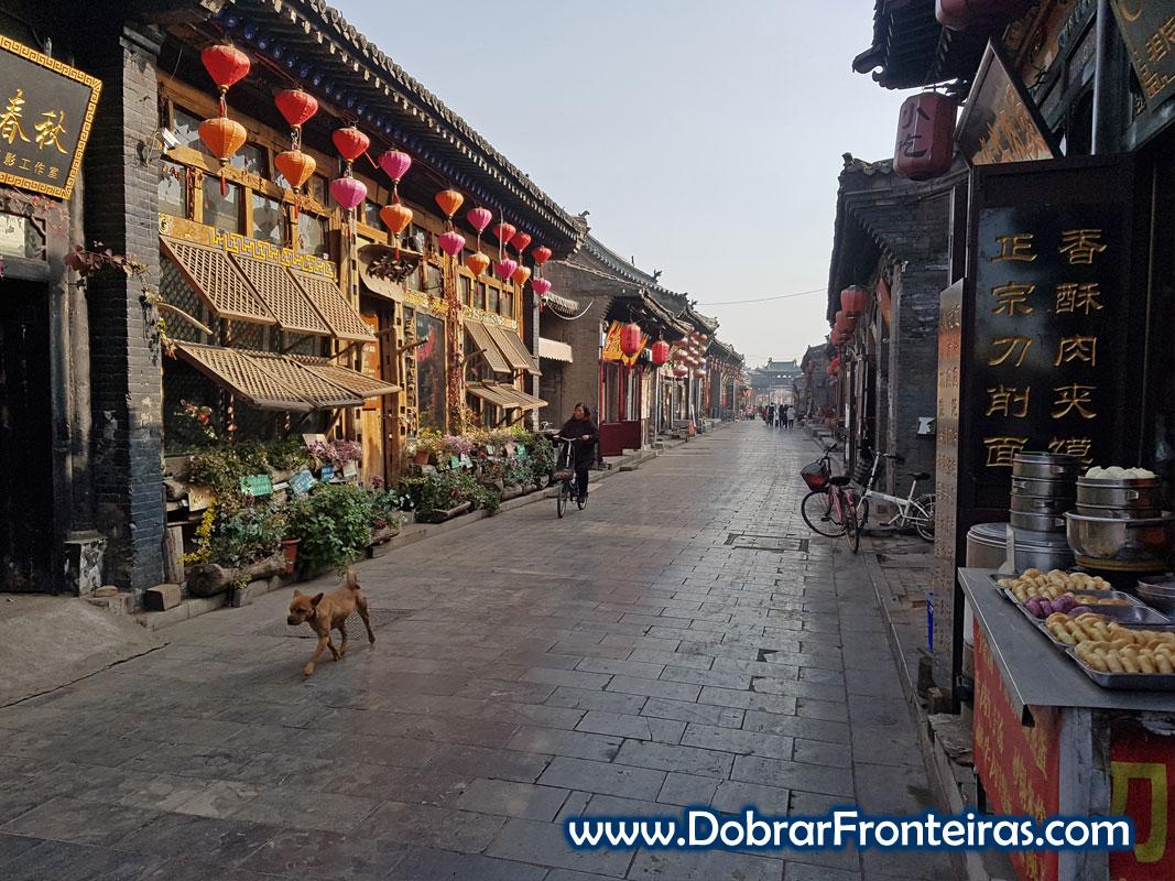 Rua ancestral chinesa em Pingyao com candeeiros vermelhos, cão e bicicleta .