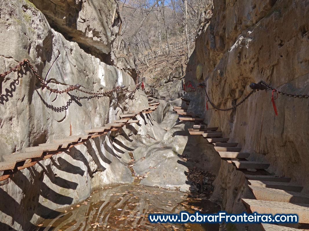 Degraus de ferro suspensos sobre ribeiro em Quixian, Mianshan, China
