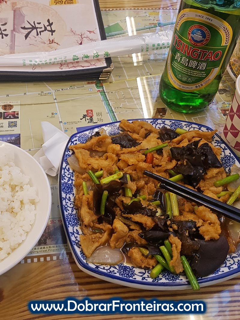 Prato como comida chinesa, arroz e cerveja Tsingtao em restaurante na cidade de Pingyao