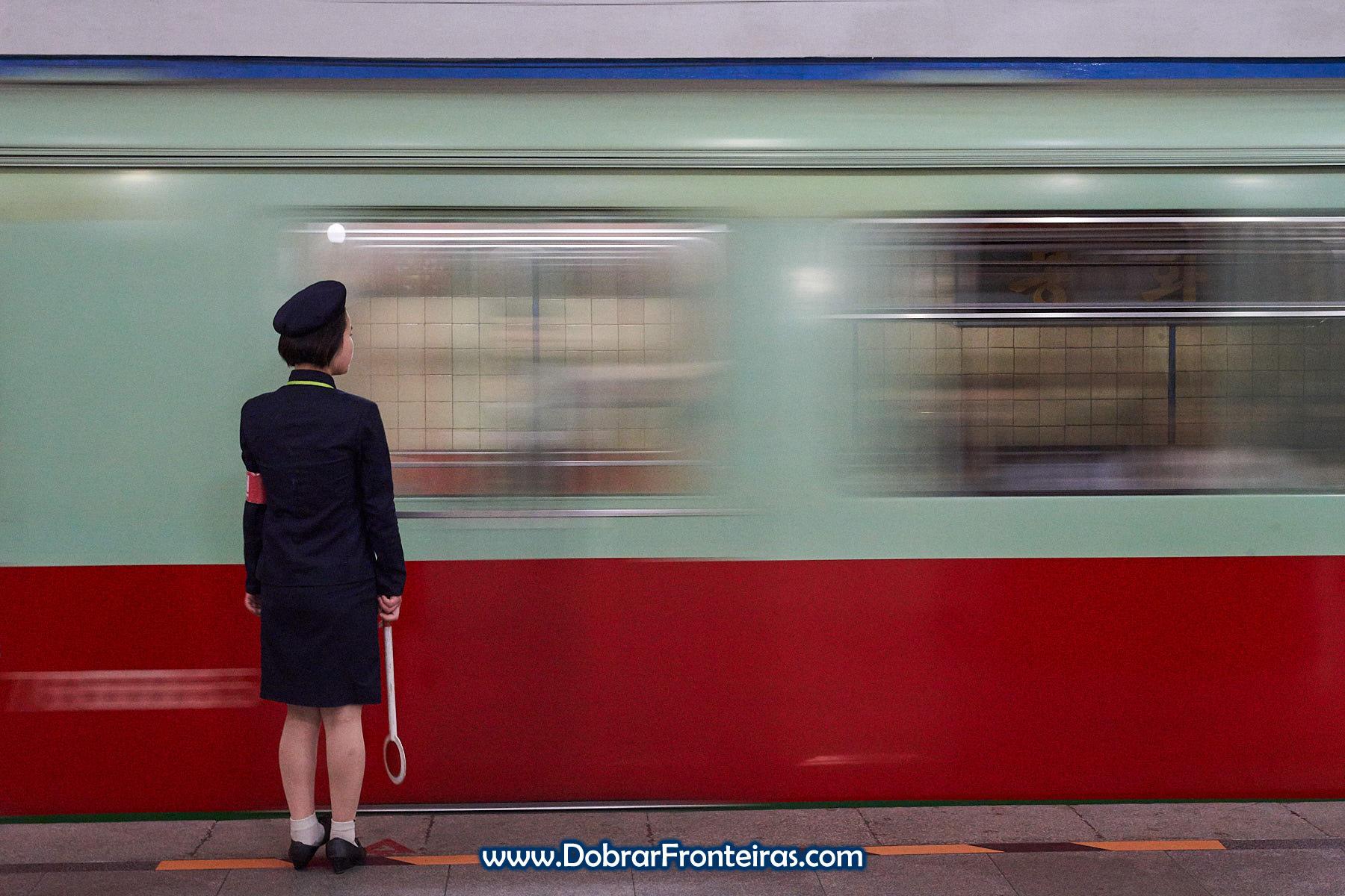 Longa exposição com funcionária de uniforme no metro de Pyongyang