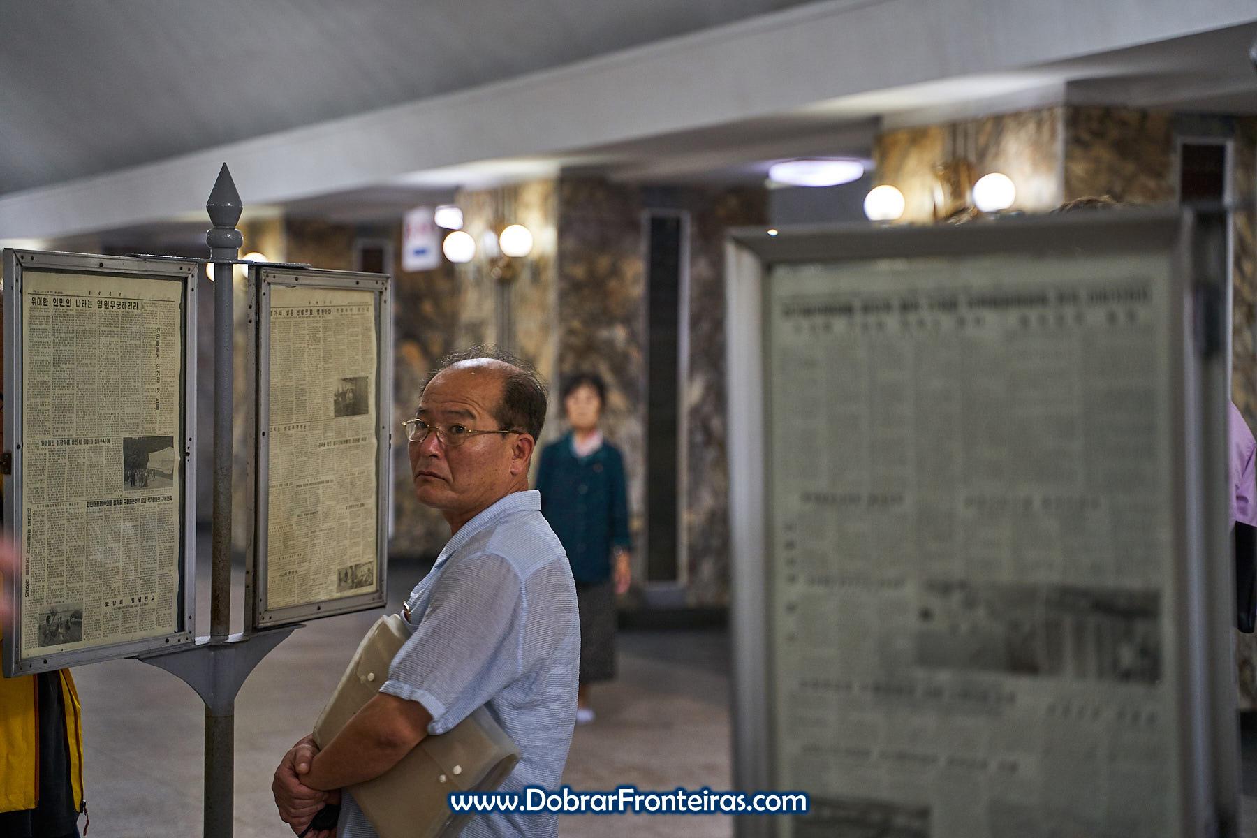 Homem com cara triste a ler jornal na estação de metro de Ponghwa, Coreia do Norte
