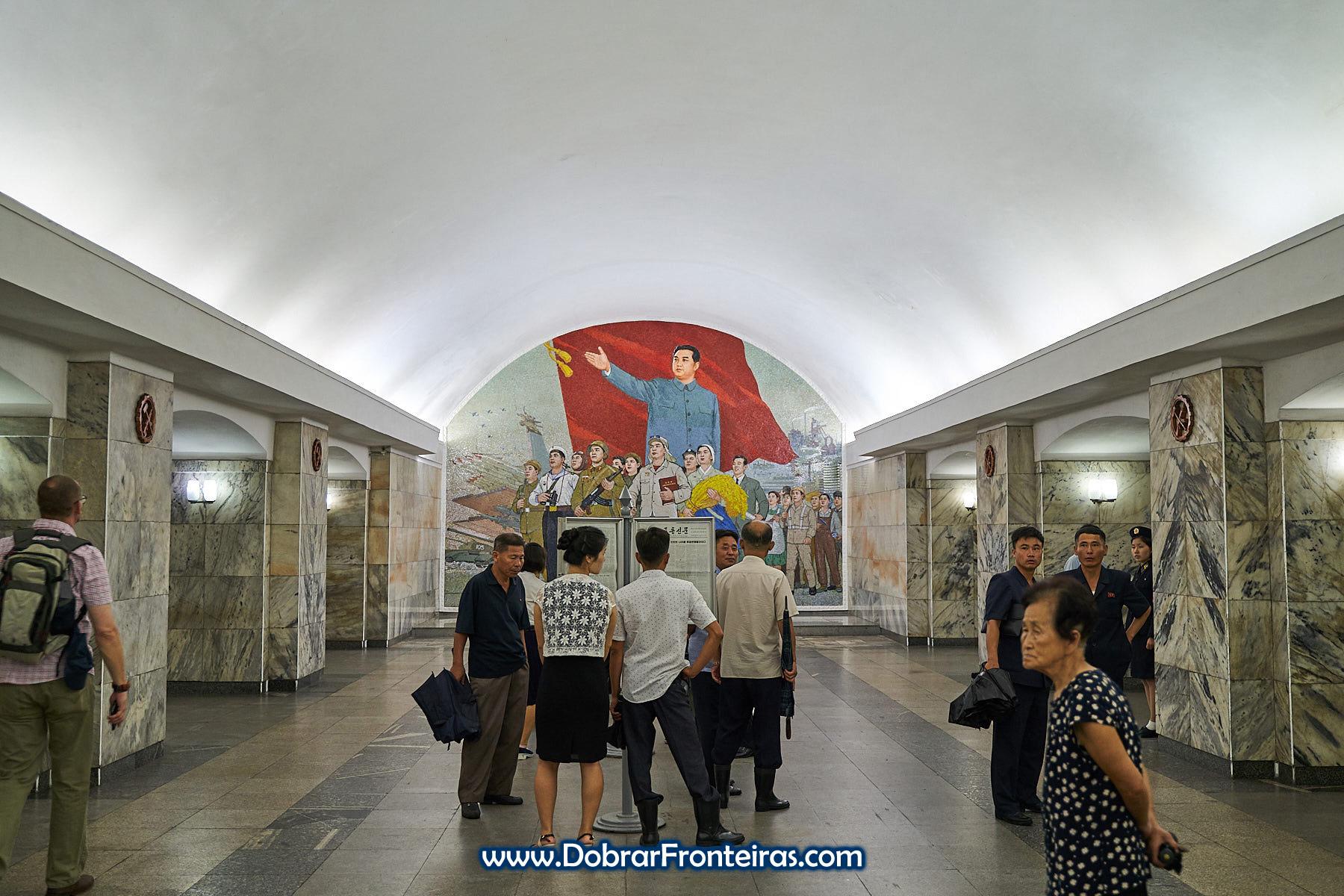 Estação de Pulgunbyol com mural de mosaico com Kim-il-Sung e alguns passageiros a ler jornal