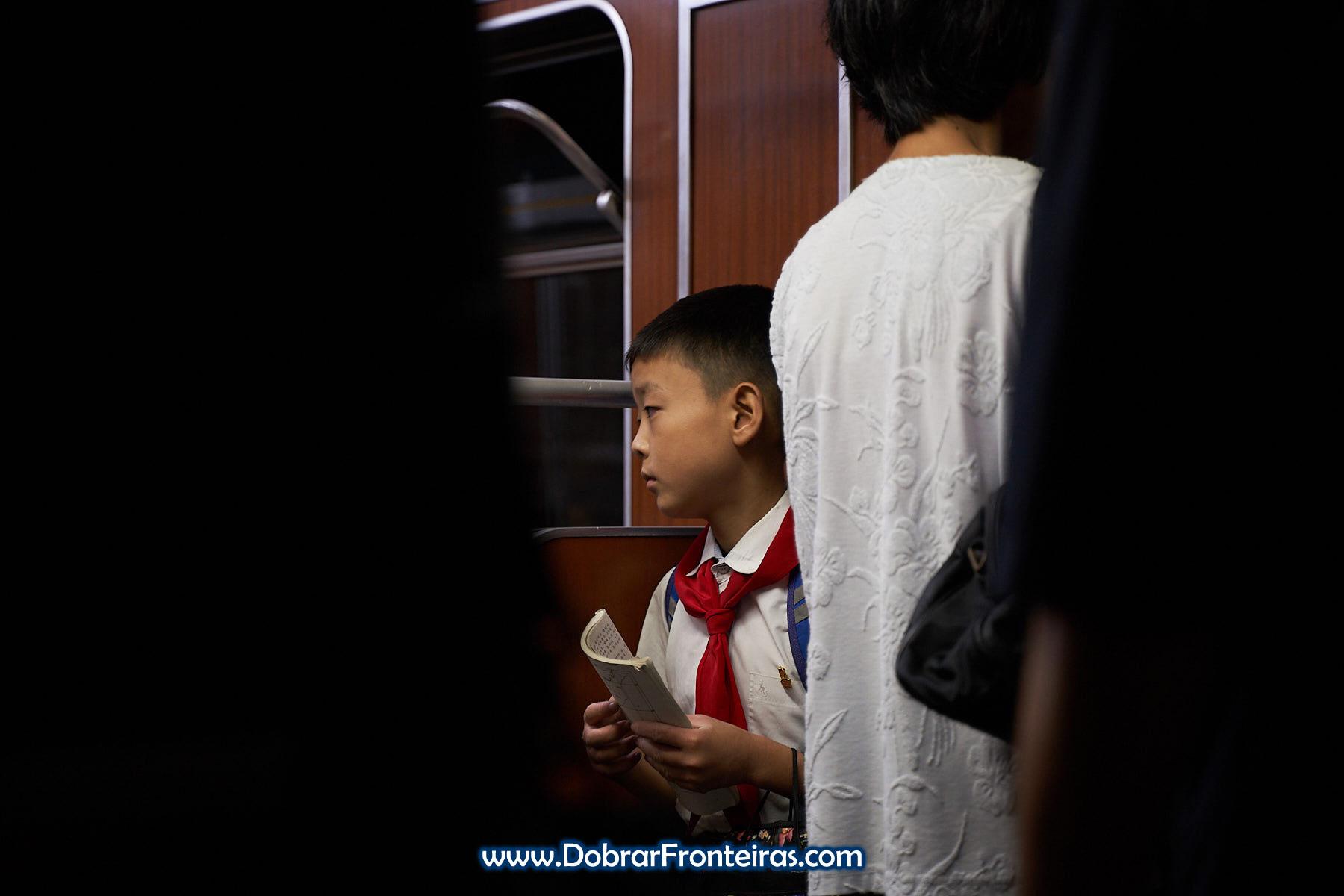 Criança com lenço vermelho de pioneiro no metro de Pyongyang, Coreia do Norte