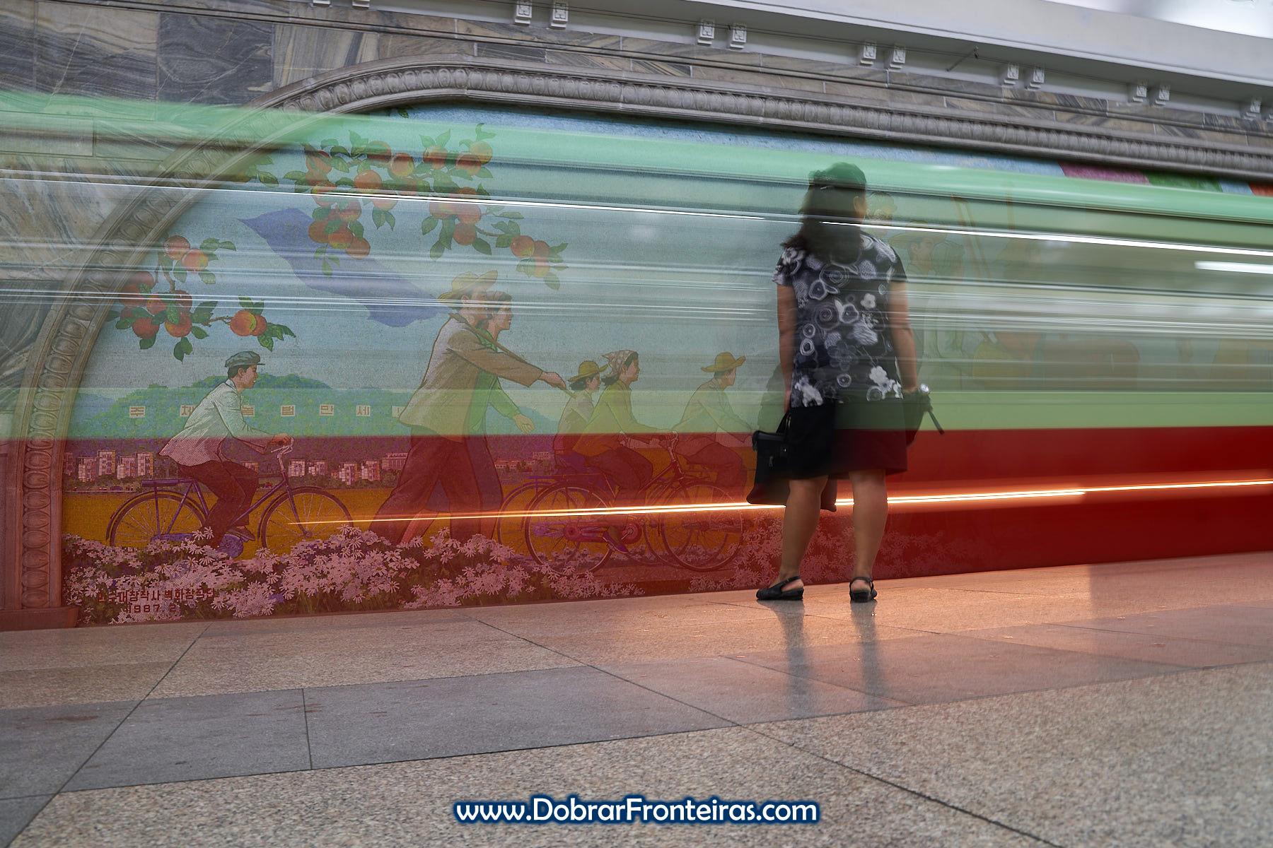 Longa exposição com comboio e mulher no metropolitano de Pyongyang