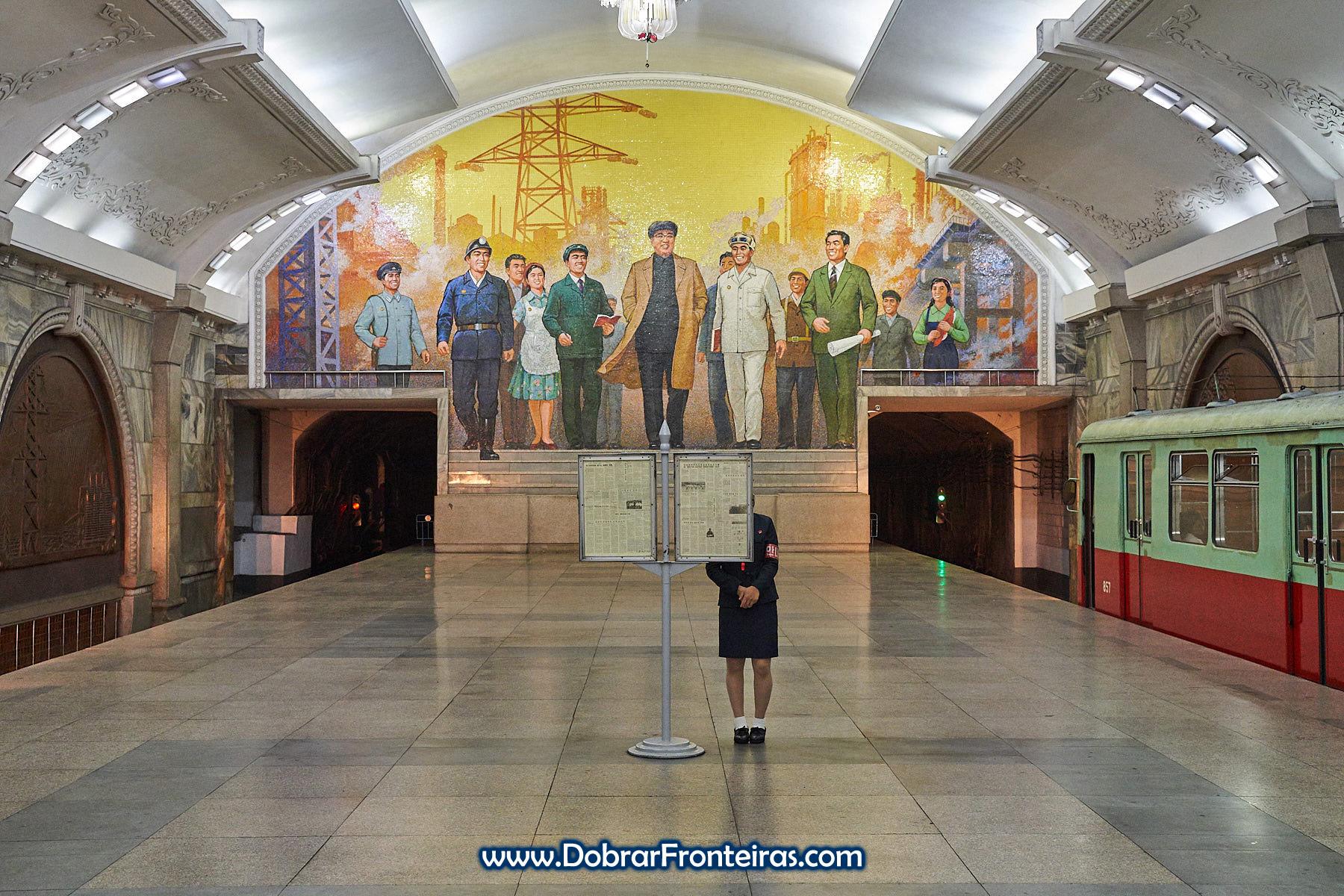 Funcionária a ler as notícias estação de Puhung, Pyongyang com mosaico e imagem de Kim-Il-Sung em fundo