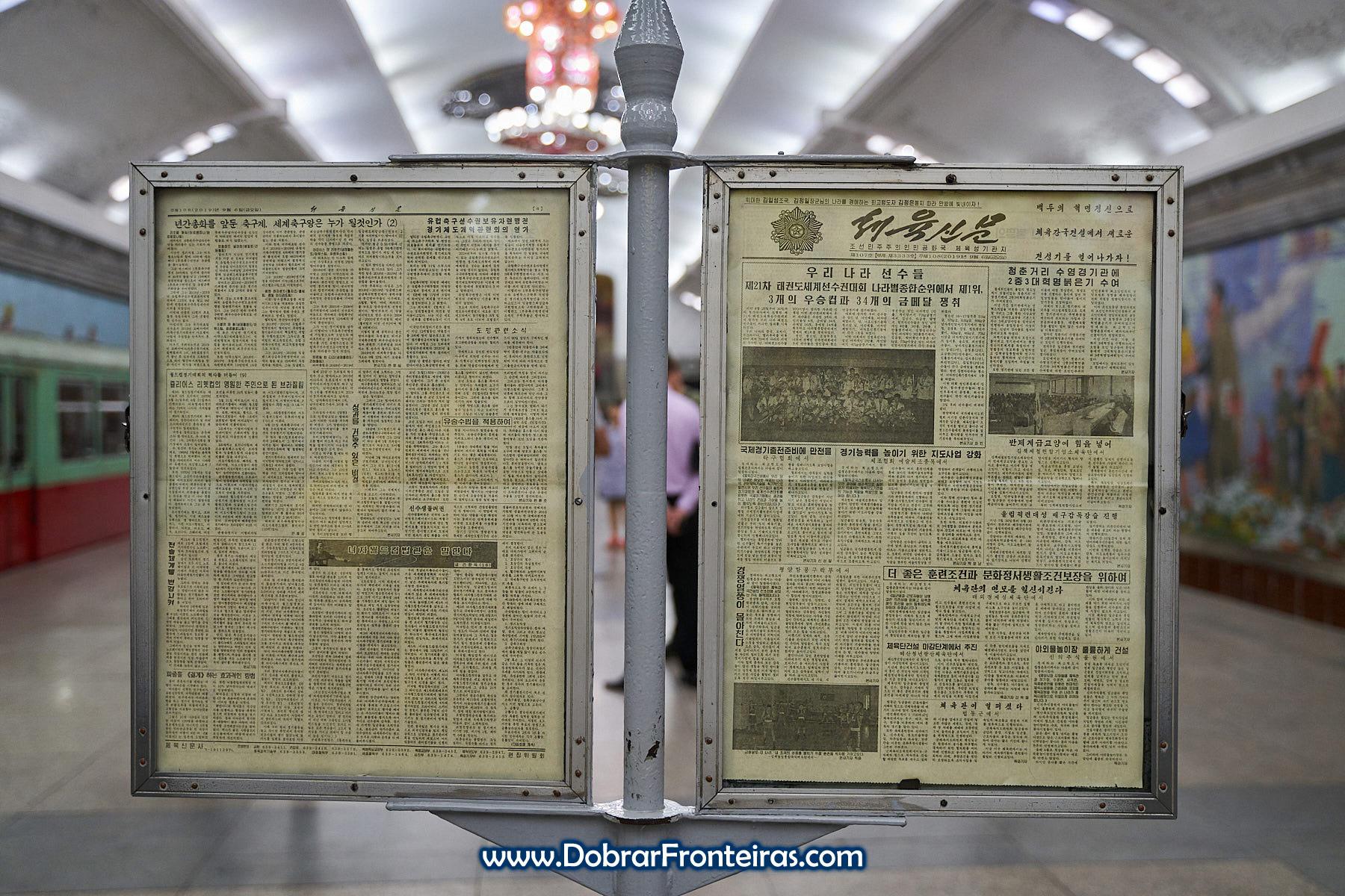 Painel com jornal no metro de Pyongyang