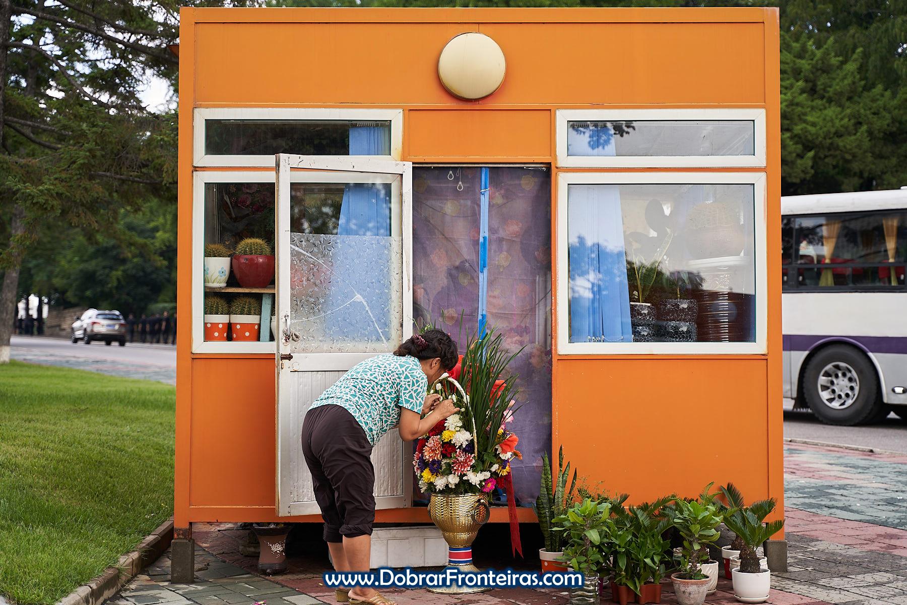 Mulher em quiosque laranja para venda de flores em Pyongyang