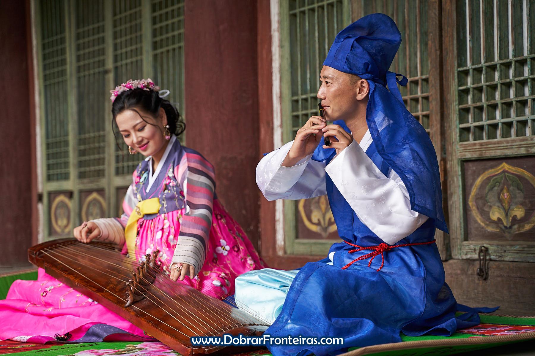 Casal de noivos com roupa tradicional da Coreia do Norte e instrumento musical