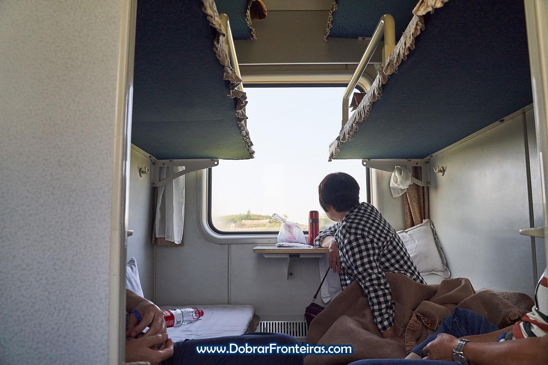 Passageiro olhando à janela em comboio norte coreano