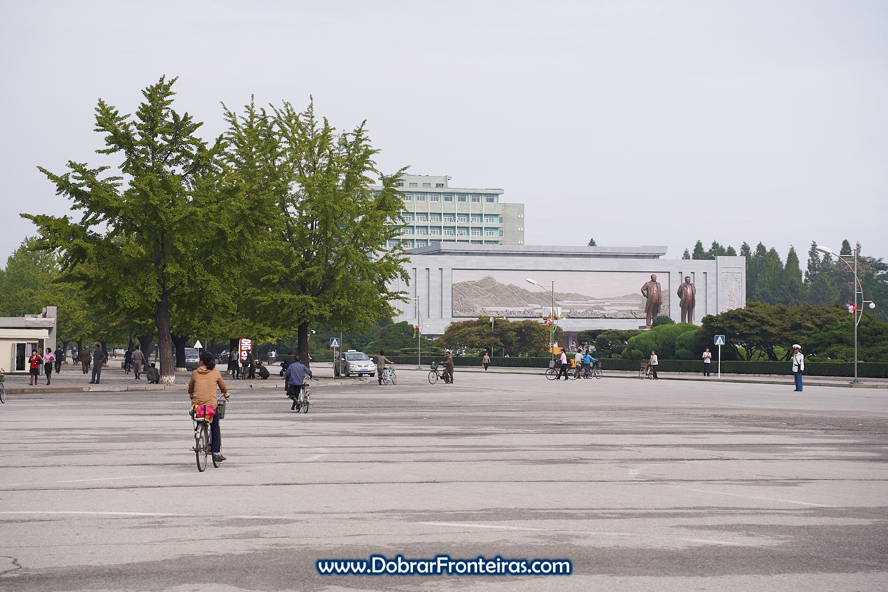 Pessoas de bicicleta em rua da Coreia do Norte com estátuas dos líderes ao fundo