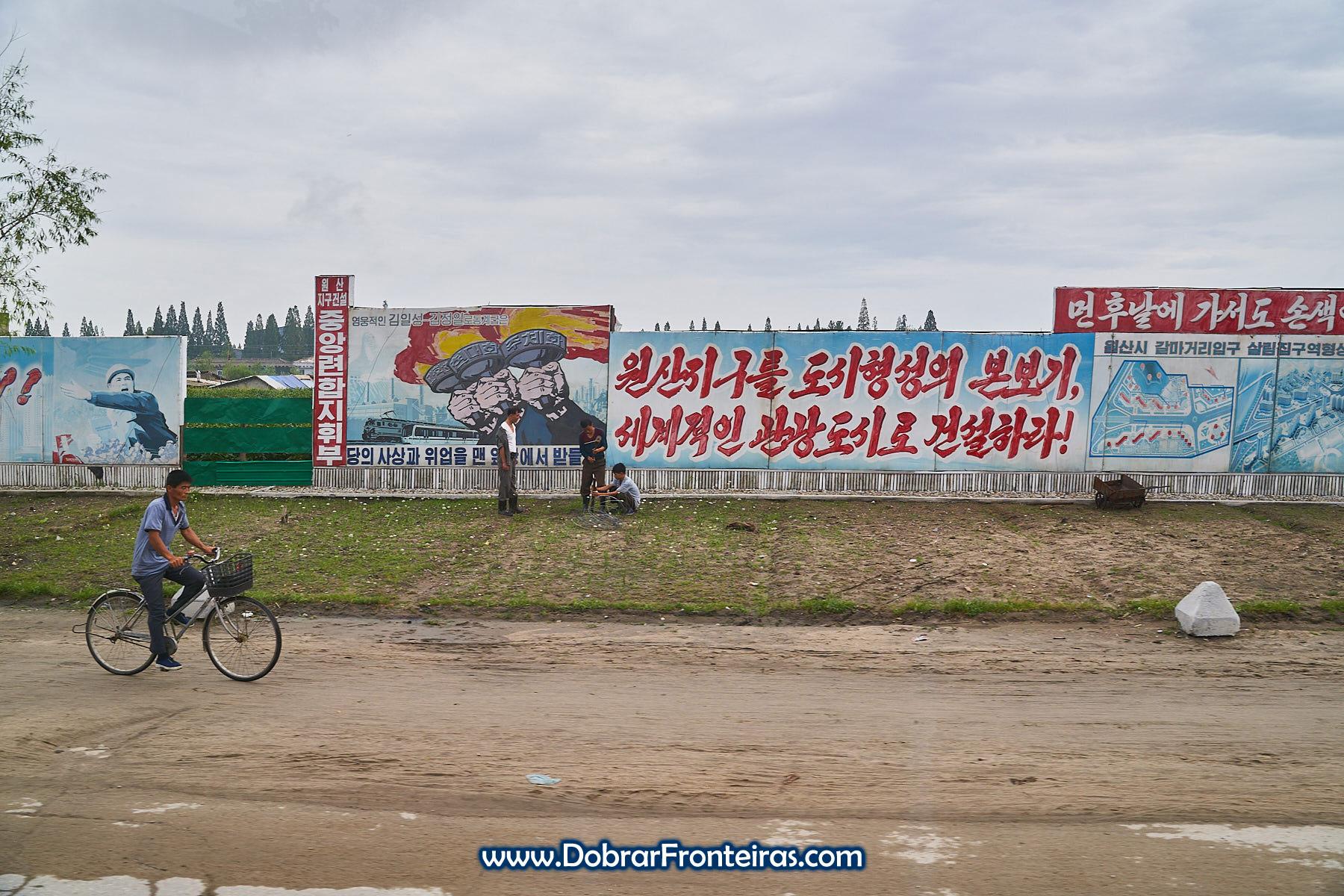 homem de bicicleta junto a cartazes de propaganda na Coreia do Norte