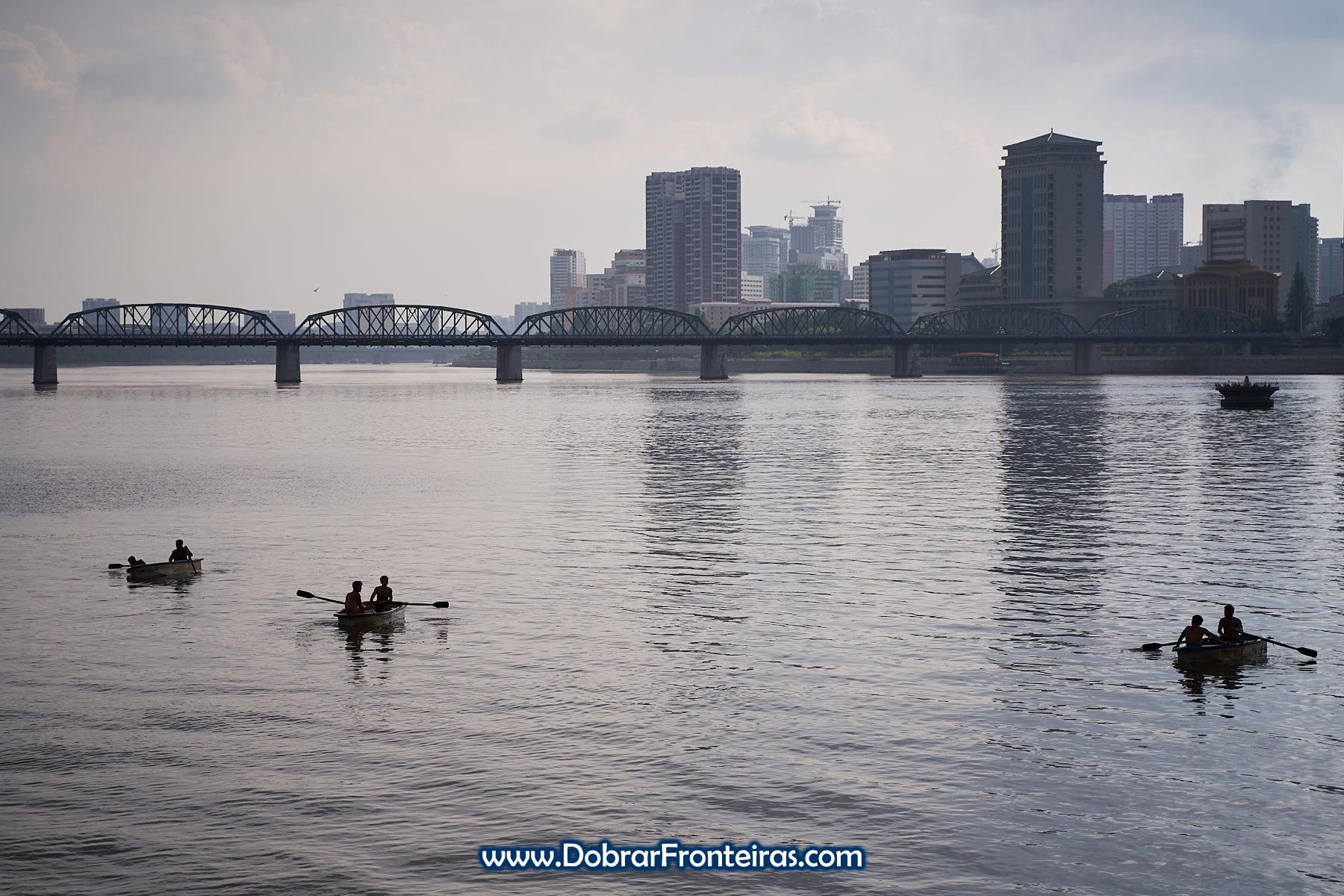Barcos no rio Taedong com ponte ao fundo