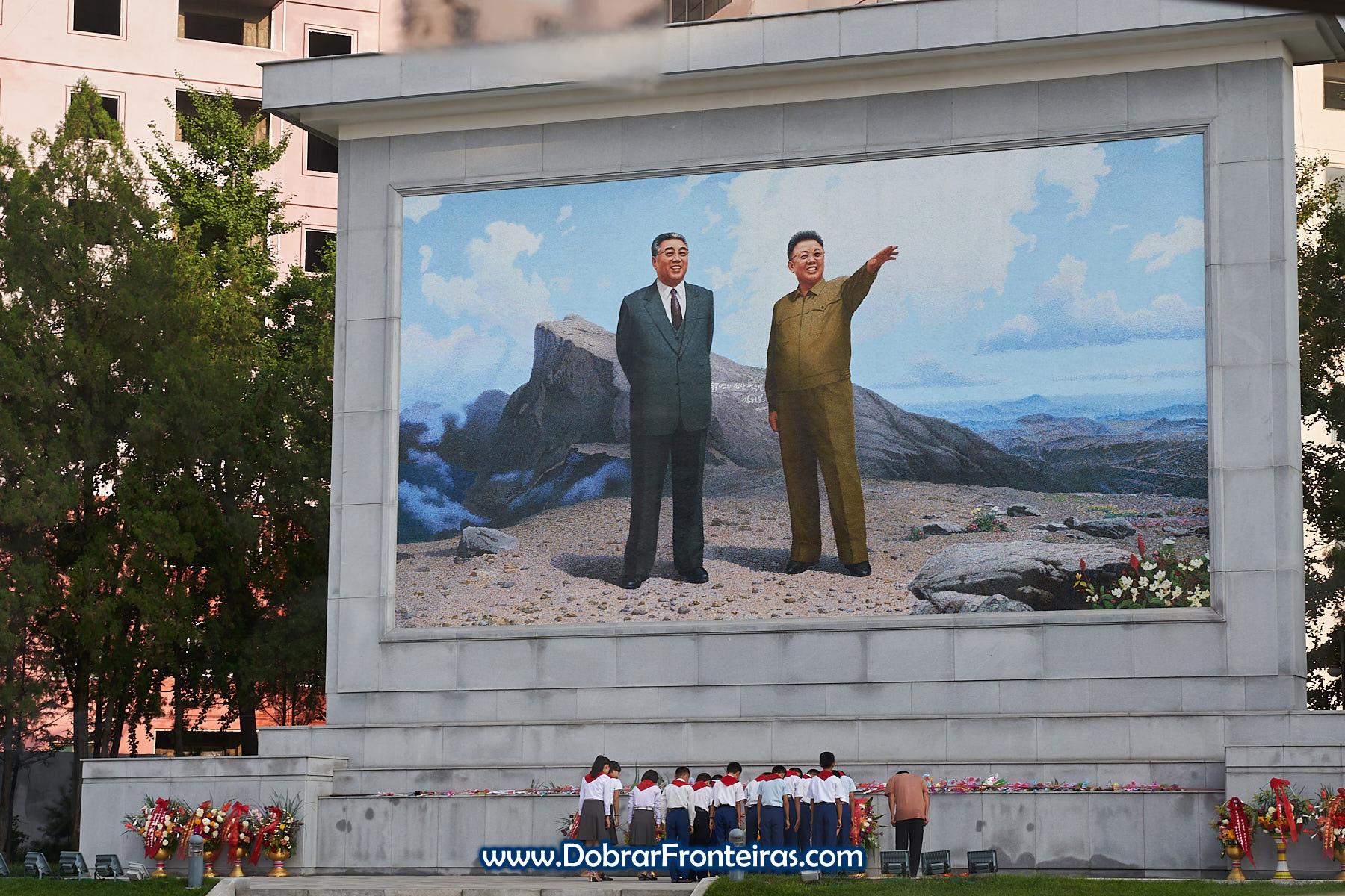 Pequenos Pioneiros junto a mural em Pyongyang