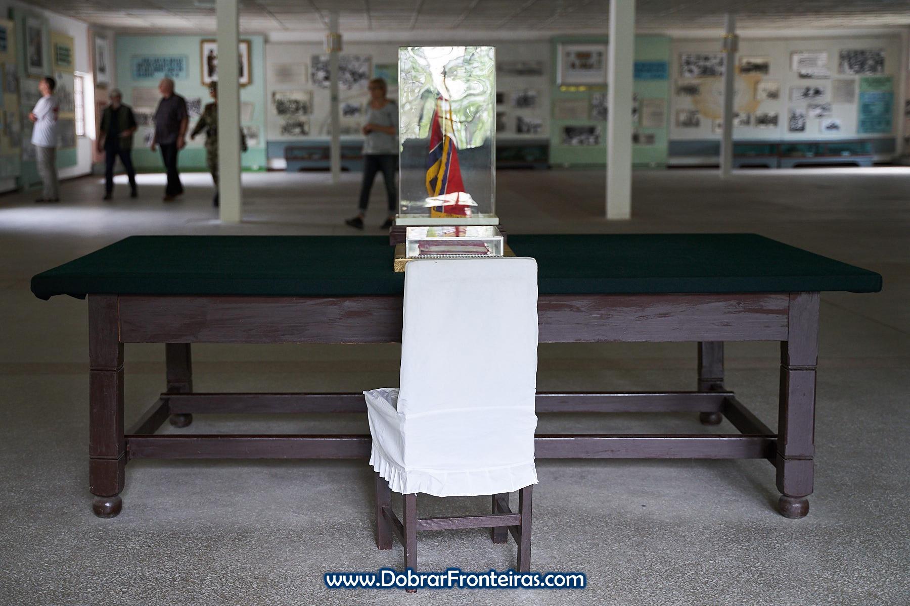 Cadeira e mesa com bandeira da Coreia do Norte e livro do armistício