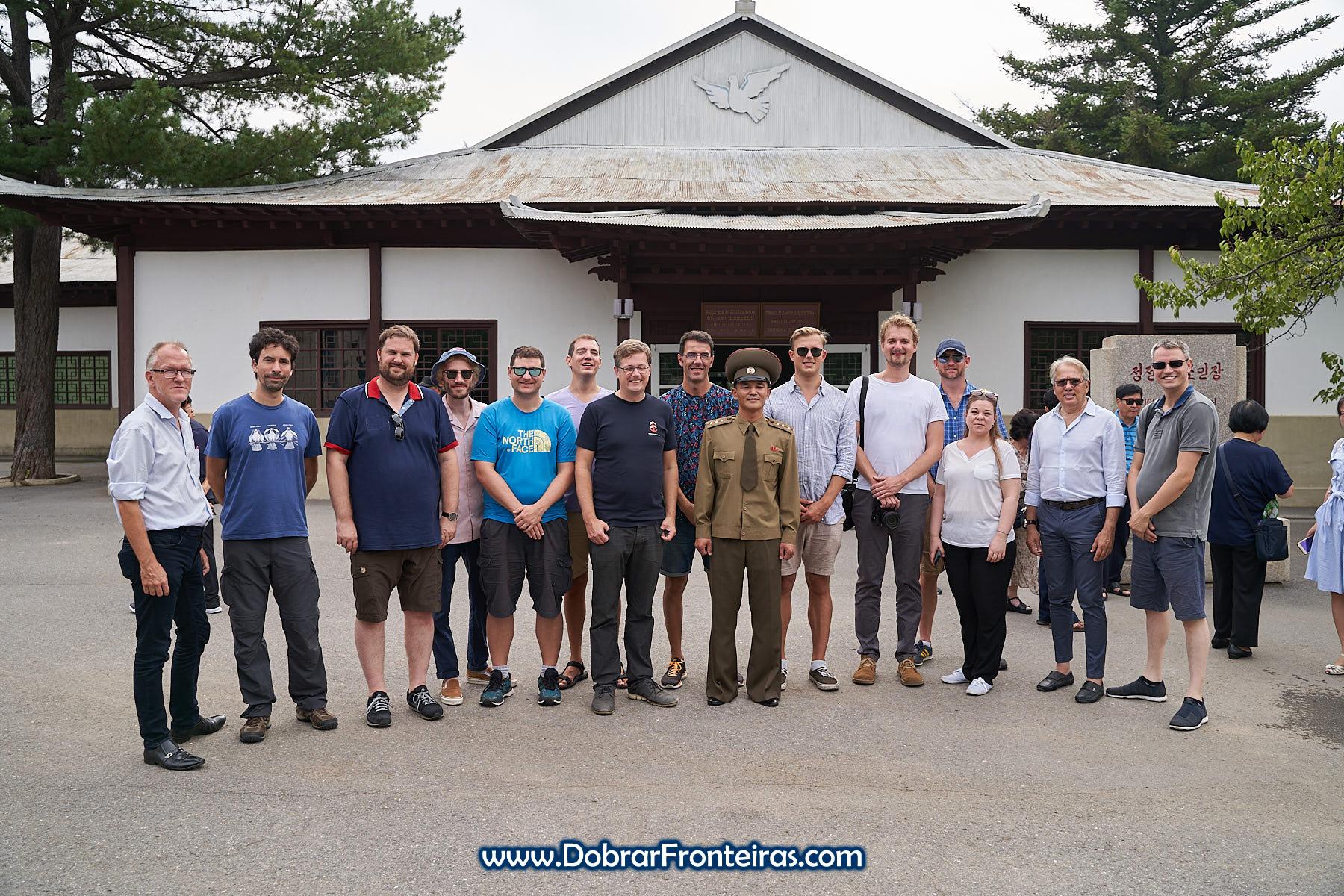 Fotografia de grupo de turistas com militar na DMZ Coreia do Norte