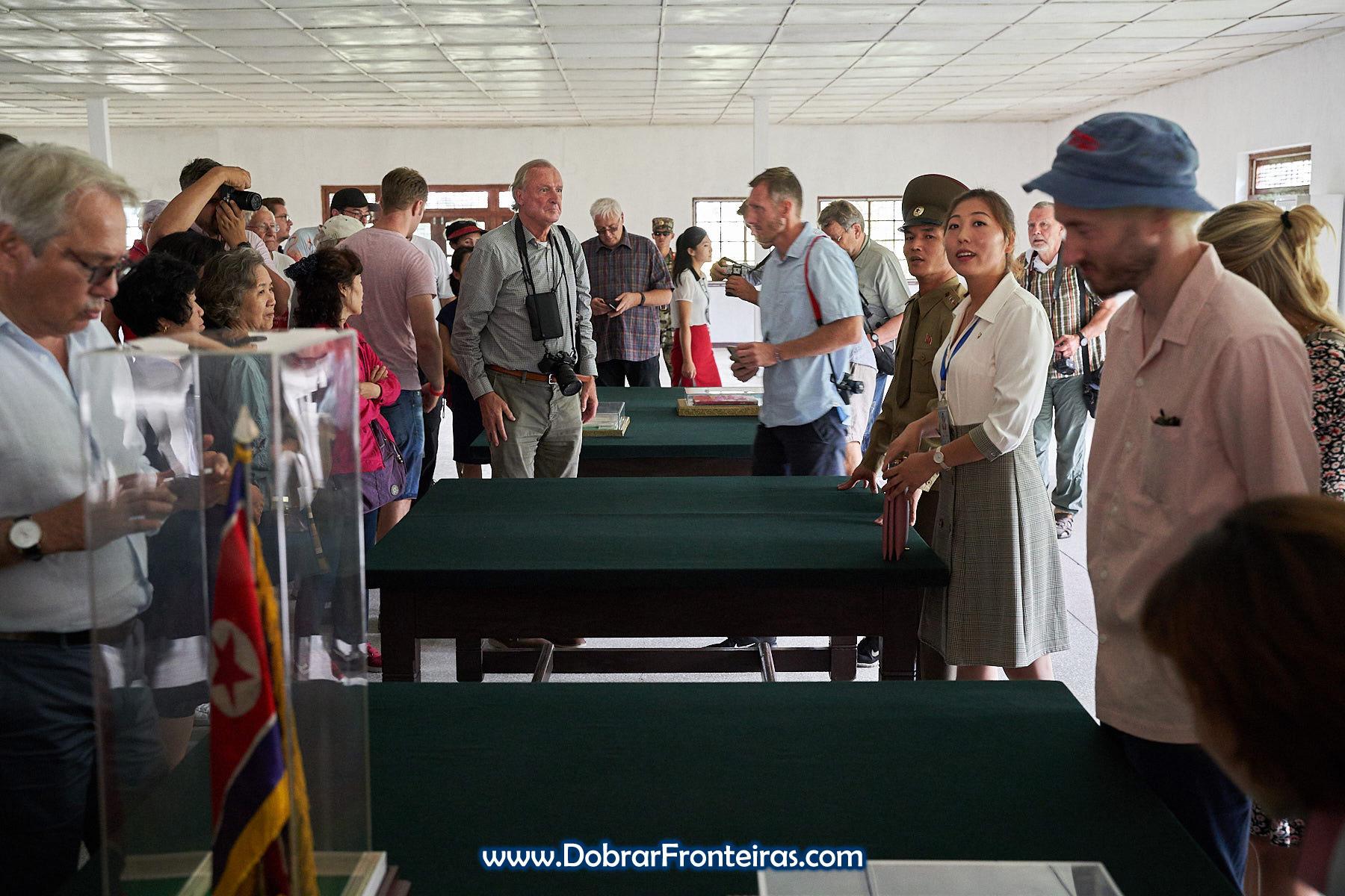 Turistas e guias na sala do armistício na DMZ
