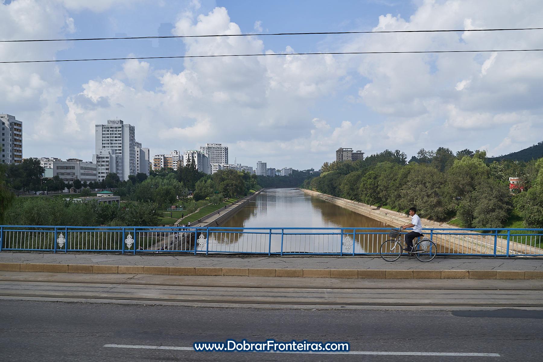 Homem de bicicleta sobre ponte em Pyongyang