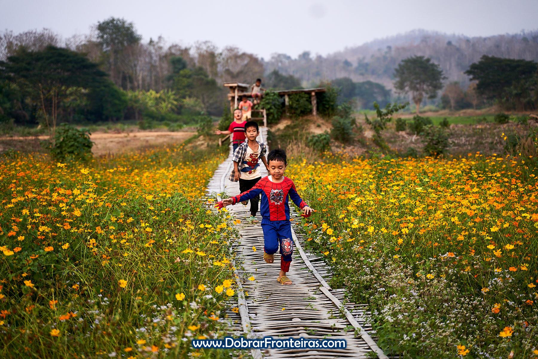 crianças a correr em passadiço de bambu sobre flores amarelas na Tailândia