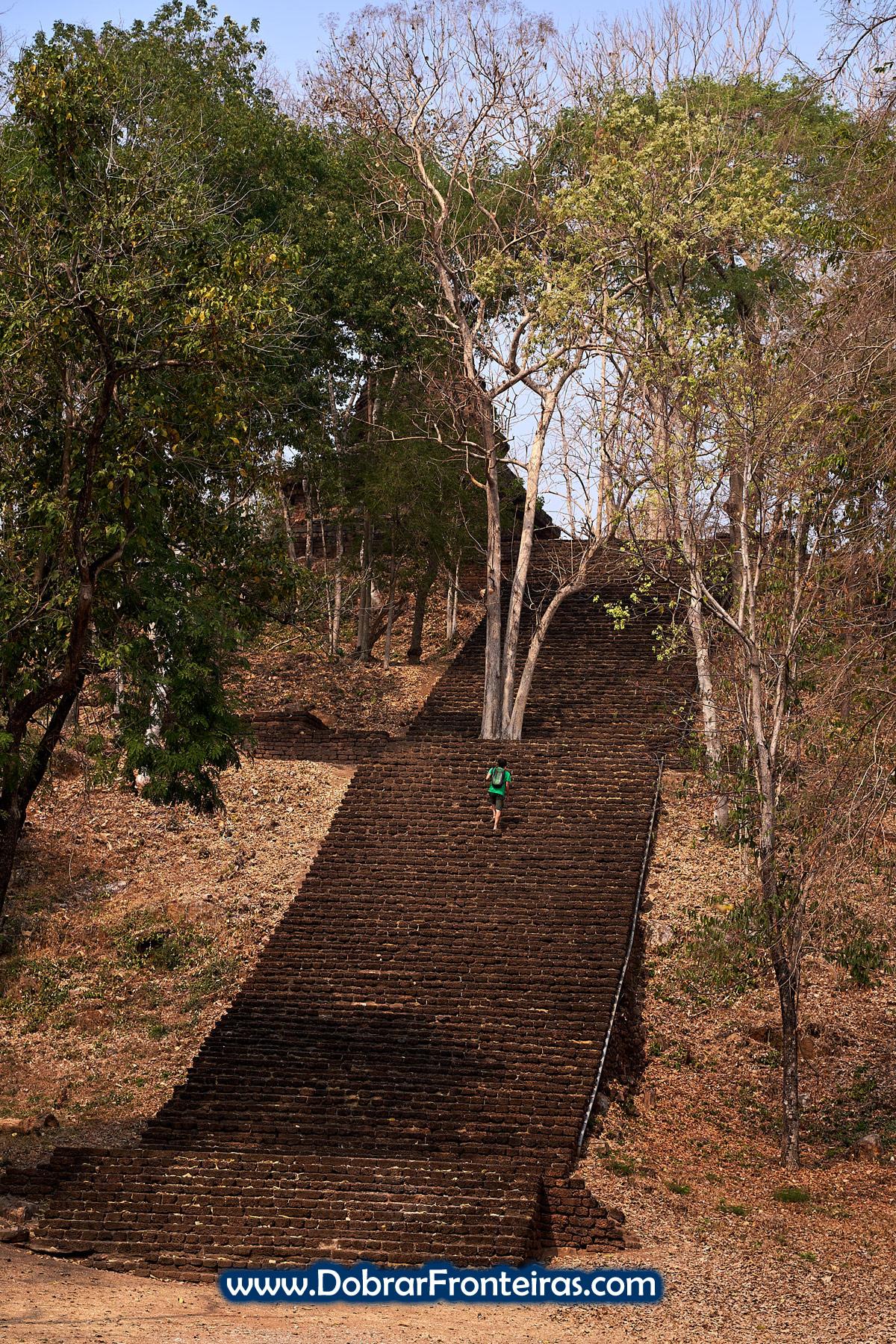 Homem a subir escada de pedra nas ruínas de Si Satchanalai