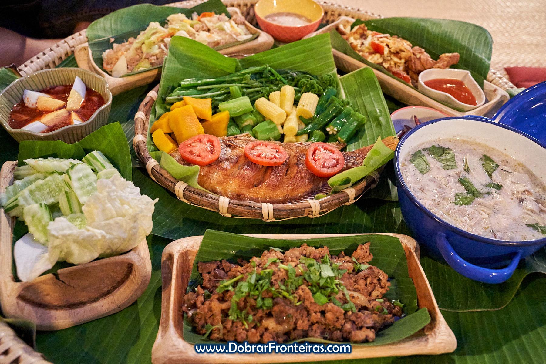refeição tailandesa com peixe sobre folhas de bananeira e bambu