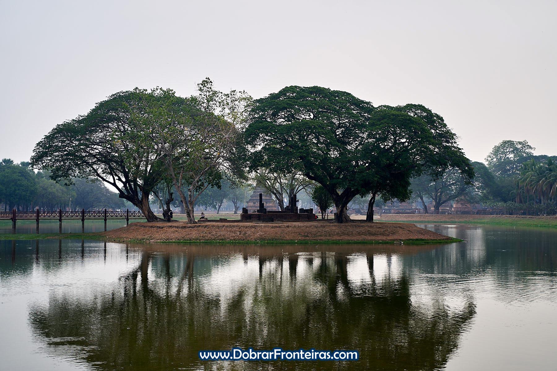 Reflexo de árvores num lago em Sukhothai