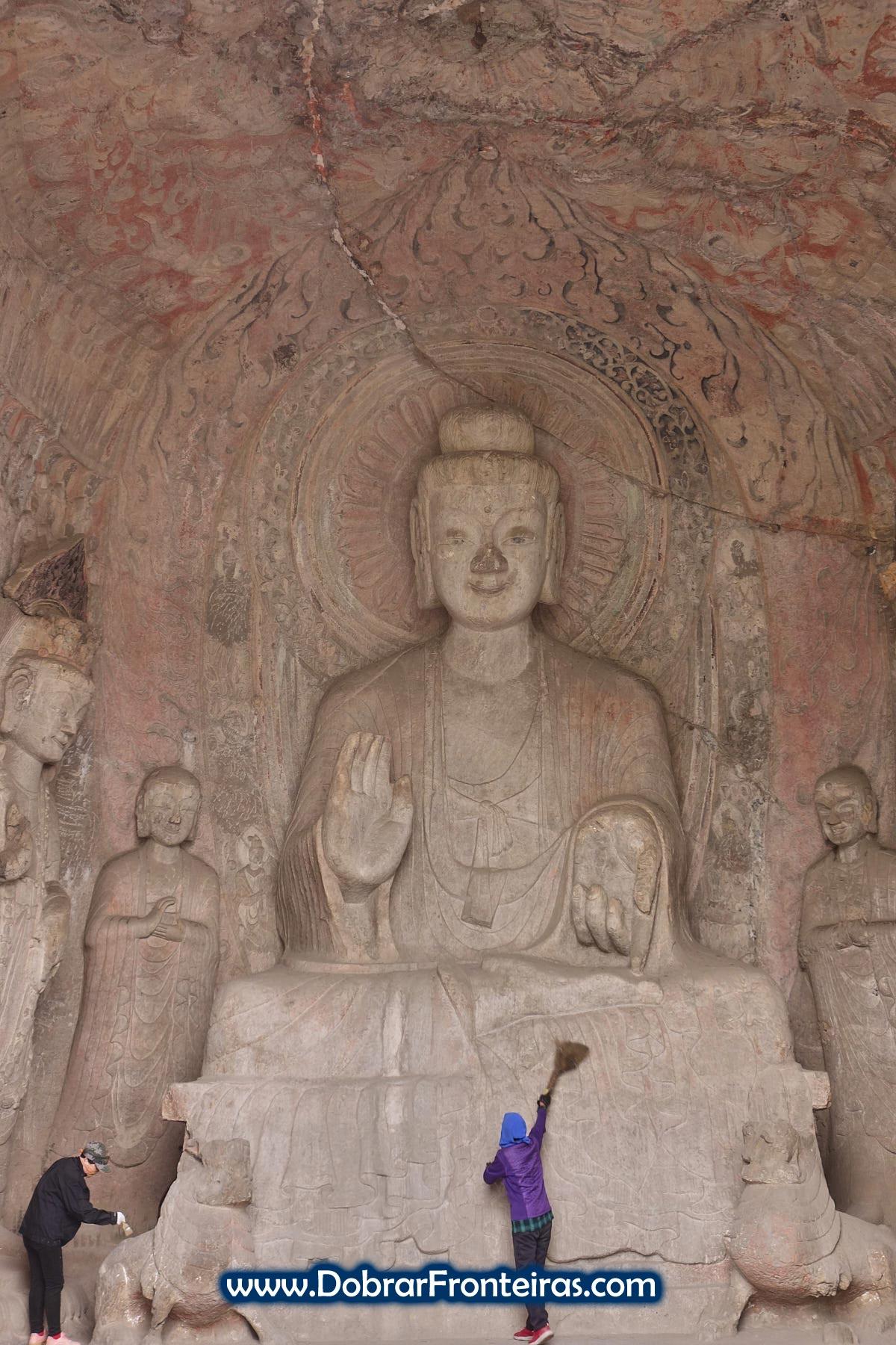 Senhoras a limpar estátua grande de Buda
