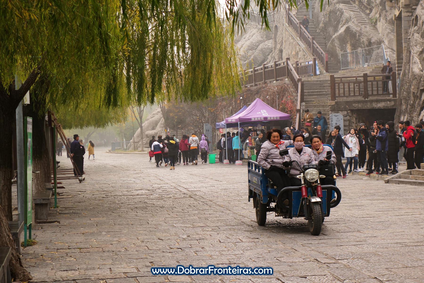 Senhoras chinesas alegres de mota junto de turistas