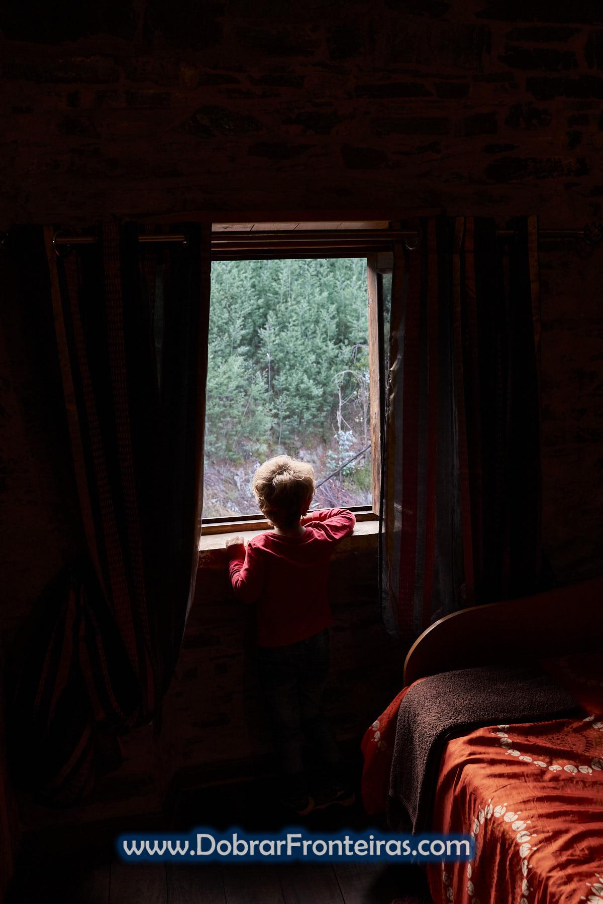 Criança a contemplar paisagem à janela