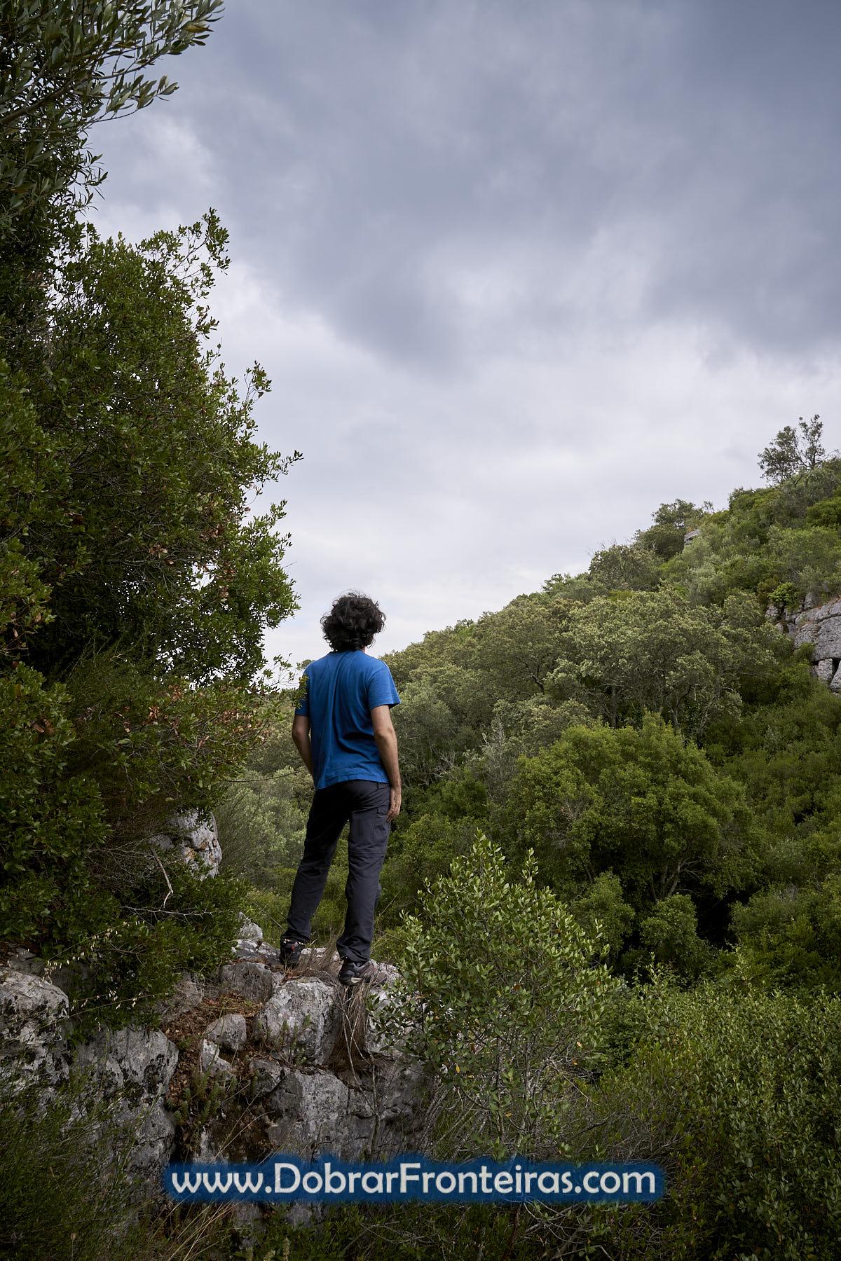 caminhante a observar paisagem sobre rocha