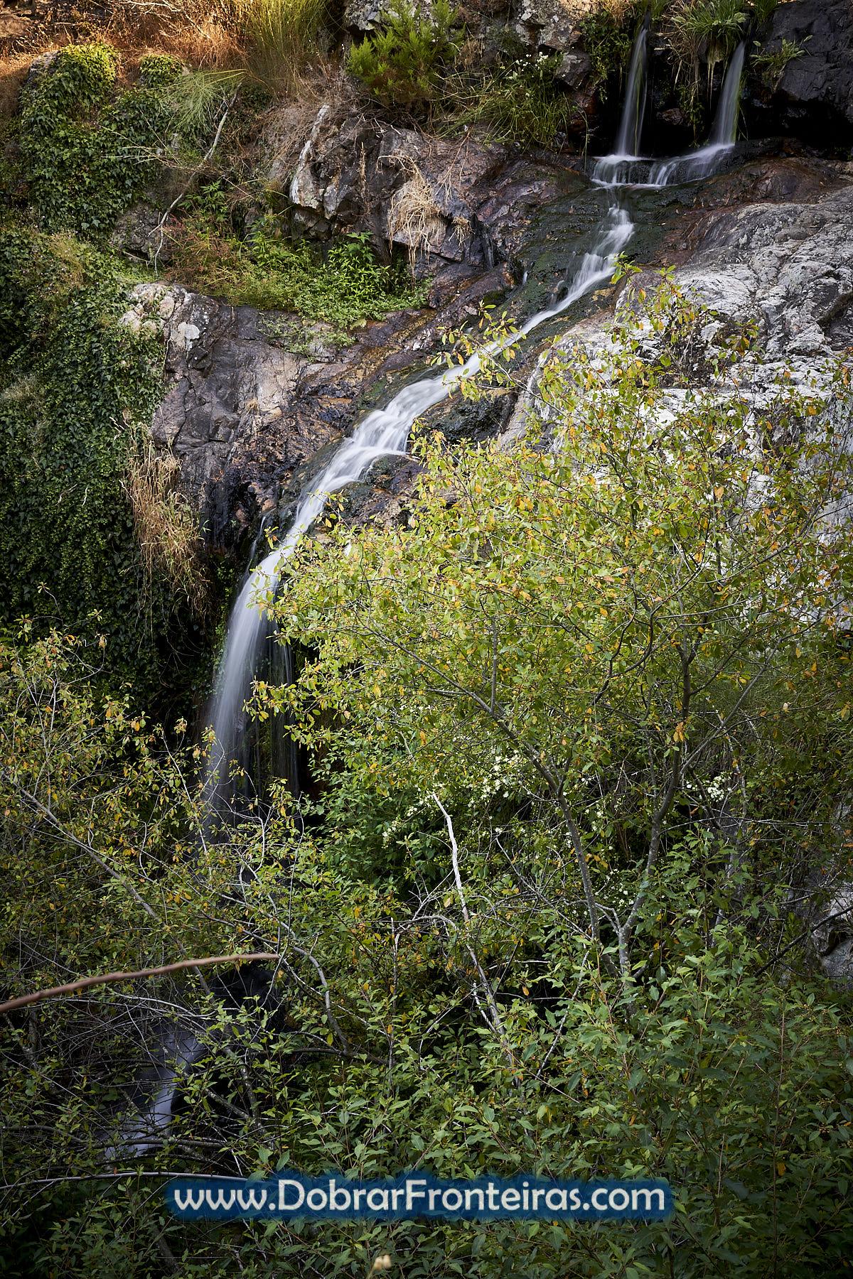 Cascata no meio de árvores em Vila de Rei