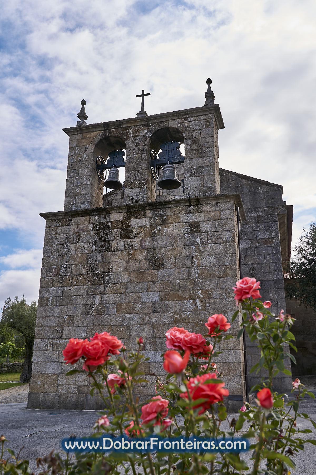 Torre de igreja com sinos e rosas